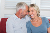 Smiling mature couple sitting on couch