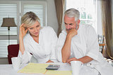 Couple sitting with home bills and calculator
