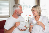 Couple with coffee cups looking at each other