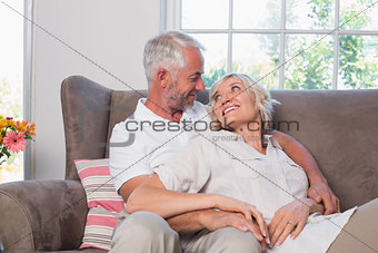 Relaxed mature couple sitting on couch
