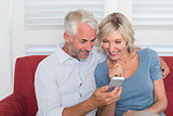 Smiling mature couple reading text message