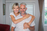 Smiling woman embracing mature man at home
