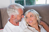 Close-up of happy relaxed mature couple on sofa