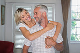 Woman embracing mature man from behind at home