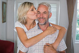 Happy woman embracing and kissing mature man