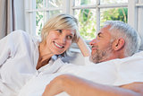 Smiling relaxed mature couple lying in bed at home