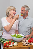 Happy woman feeding mature couple salad in kitchen