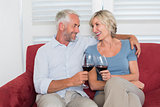 Relaxed mature couple toasting wine glasses in living room