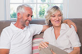 Happy relaxed mature couple sitting on sofa