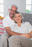 Relaxed mature couple sitting on sofa in living room