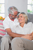 Relaxed mature couple sitting on sofa