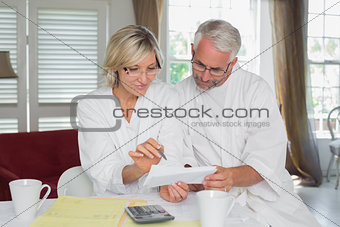 Mature couple sitting with home bills and calculator
