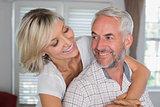 Close-up of a happy woman embracing mature man