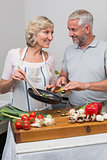 Mature couple preparing food together in kitchen