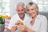 Happy mature couple with a flower in living room