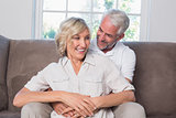 Mature man embracing woman from behind in living room