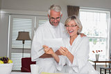 Cheerful couple looking at a document at home