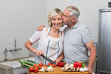 Man kissing woman as she chops vegetables in kitchen