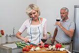 Mature man with wine glass and woman chopping vegetables in kitchen