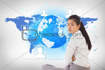 Composite image of businesswoman sitting cross legged frowning