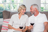 Happy relaxed mature couple with wine glasses in living room