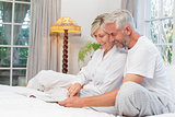 Relaxed mature couple reading book in bed