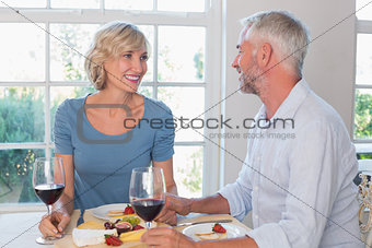 Mature couple with wine glasses having food