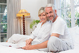 Portrait of a relaxed happy mature couple with book in bed
