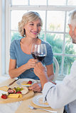 Mature couple toasting wine glasses over food