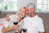 Loving mature couple with wine glasses in living room