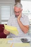 Serious man sitting with home bills and calculator