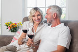 Happy loving mature couple with wine glasses in living room