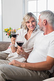 Happy mature couple with wine glasses in living room