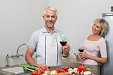 Mature couple with wine glasses preparing food in kitchen