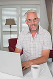 Smiling mature man using laptop at home