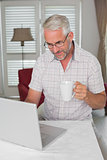 Casual mature man using laptop while drinking coffee