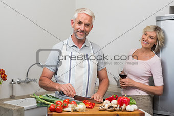 Mature man chopping vegetables while woman with wine glasses in kitchen