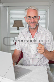 Mature man using laptop while drinking coffee