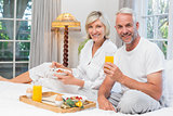 Mature couple having breakfast in bed