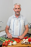Portrait of a mature man chopping vegetables in kitchen