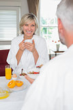 Smiling mature woman having breakfast with cropped man