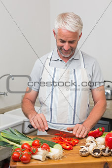 Mature man chopping vegetables in kitchen