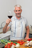 Mature man with wine glass while chopping vegetables in kitchen