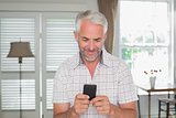 Relaxed mature man text messaging