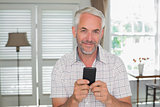 Smiling relaxed mature man text messaging