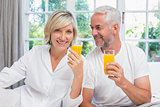Happy mature couple holding orange juices