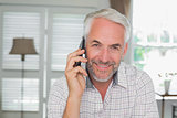 Relaxed mature man using mobile phone at home