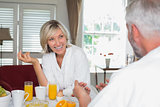 Cheerful woman having breakfast with cropped man