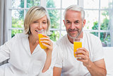 Mature couple holding orange juices at home