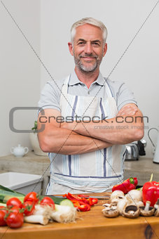 Portrait of a mature man with vegetables in kitchen